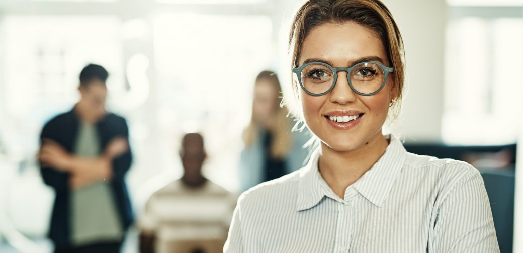 Smiling young businesswoman with colleagues working in the background